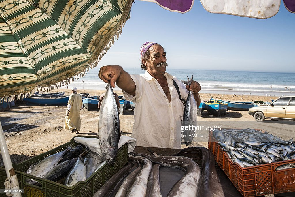 Fisherman selling his fish at market on the beach,