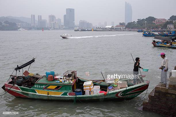 Fisherman sells seafood to tourists on the shore of Gulangyu Island on November 12 2014 in Xiamen China Xiamen is located on the southeast coast of...
