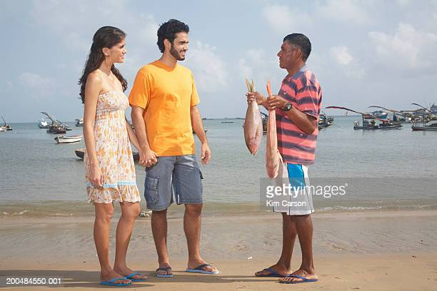 Fisherman showing young couple red snappers on beach