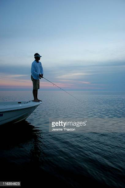 Fisherman silhouette from his boat at dusk in the Gulf of Mexico.