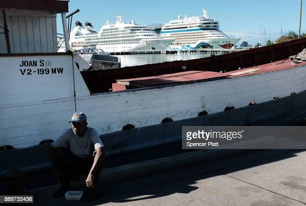 A fisherman sits by a boat in the harbor on December 10 2017 in St John's Antiqua While it's sister island Barbuda was nearly destroyed by Hurricane...