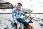 Fisherman sits on deck of boat with mast and sail