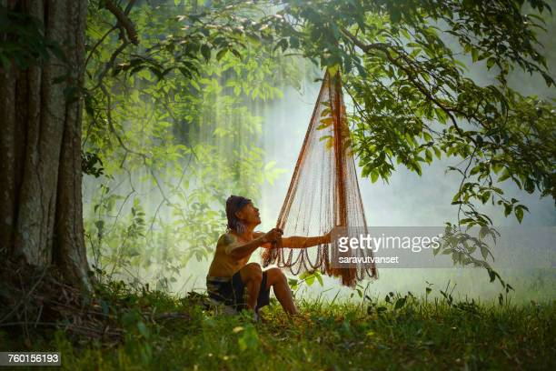 Fisherman sitting in forest inspecting fishing net, Thailand