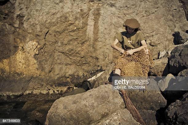 Fisherman sitting on rocks repairing nets Illyrian civilisation mid3rd century BC Historical reenactment