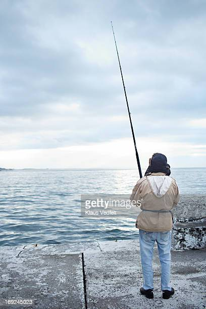Fisherman standing at harbour with fishing rod