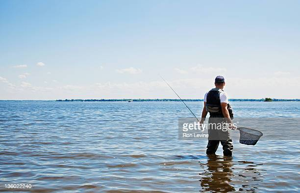 Fisherman standing in lake with net & rod