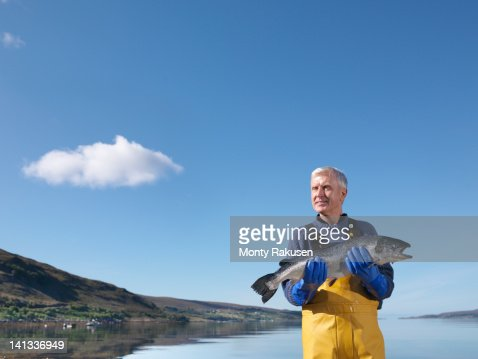 Fisherman standing in loch holding freshly caught salmon : ストックフォト