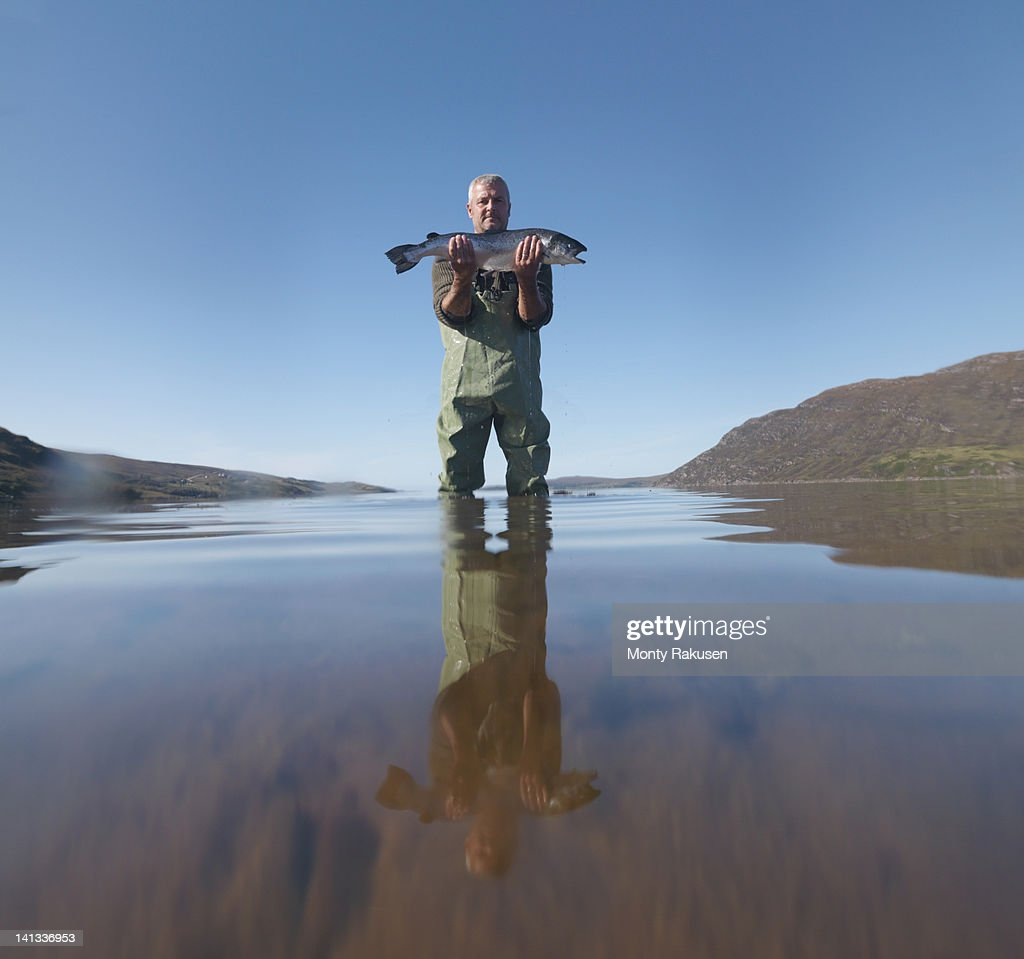 Fisherman standing in loch with freshly caught salmon