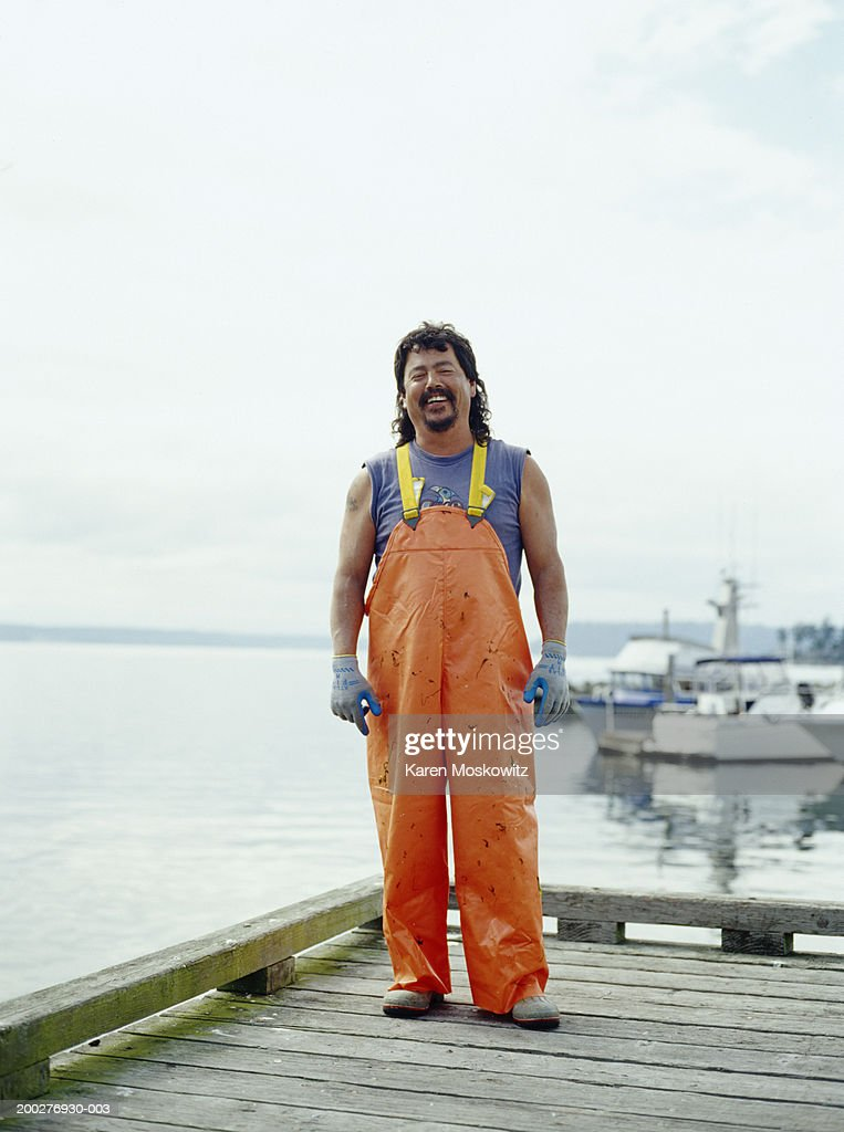 Fisherman standing on dock, smiling, portrait : Stock Photo