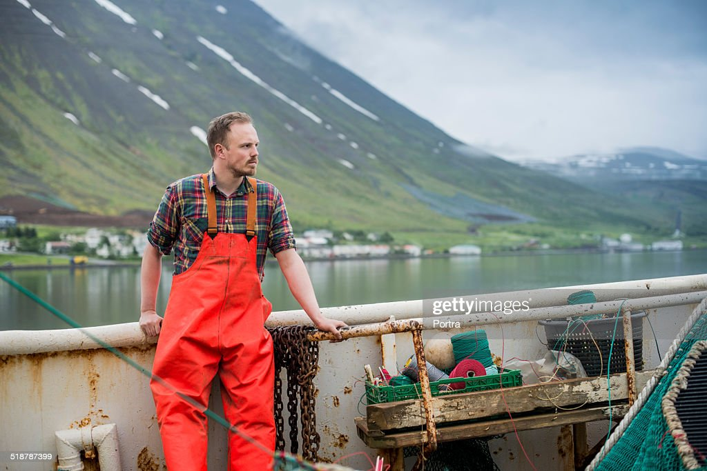 Fisherman standing on fishing boat