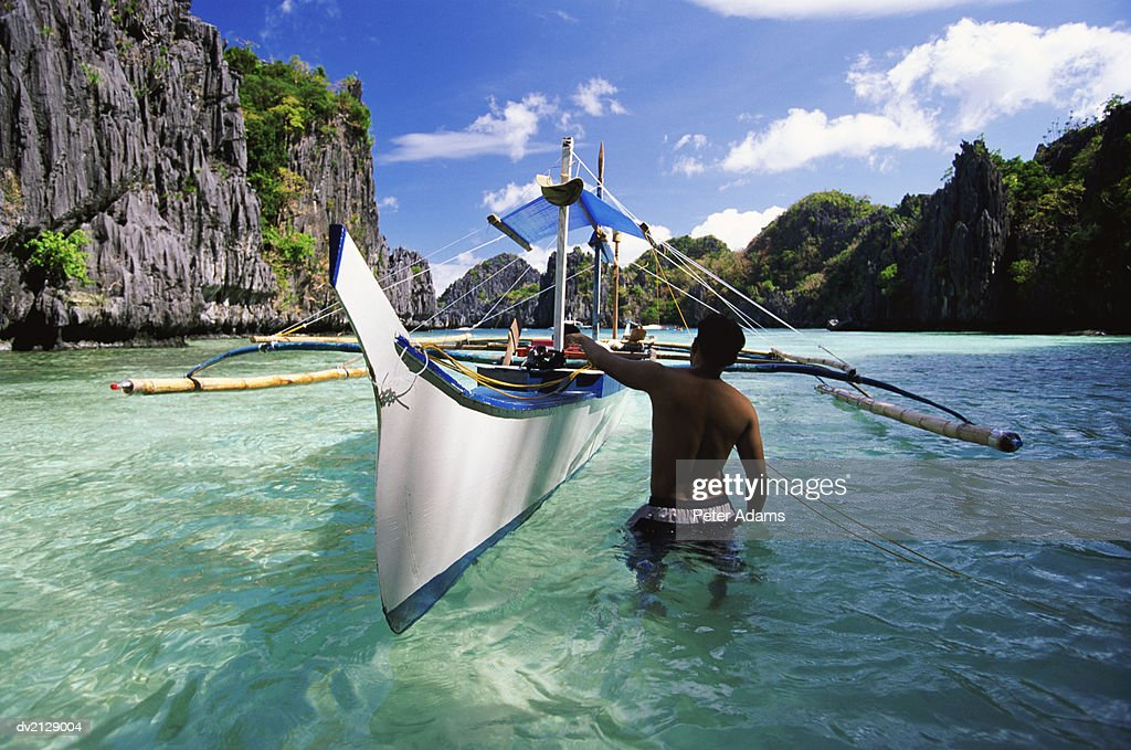 Fisherman Stands in a Lagoon, Pushing His Fishing Boat Along : Stock Photo