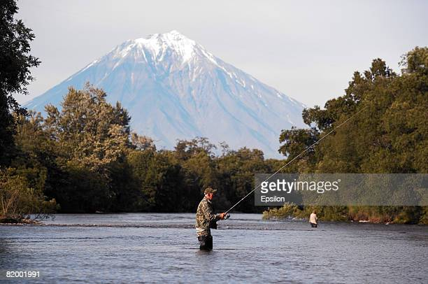 A fisherman stands knee deep in a river August 19 2007 in Kamchatka peninsula Russia