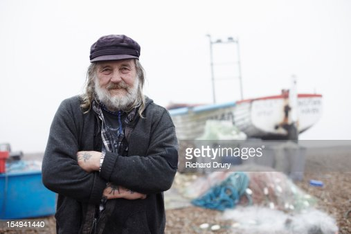 Fisherman stood by fishing boat and nets : Stock Photo