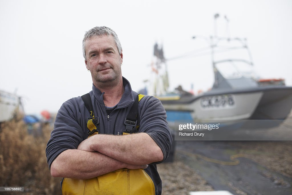 Fisherman stood by his boat : Stock Photo