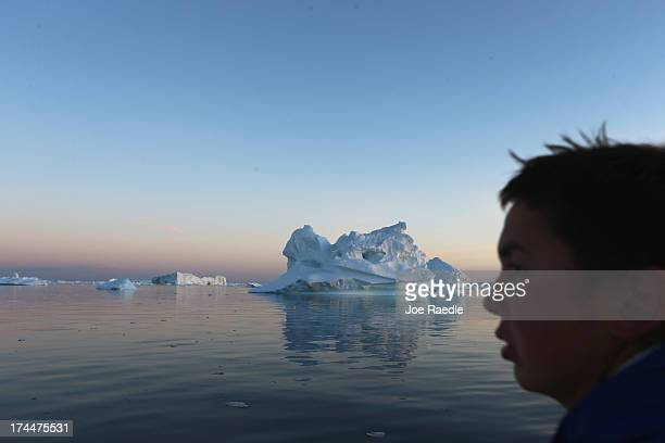 Fisherman Sune Jerimiassen navigates his boat around icebergs that broke off from the Jakobshavn Glacier on July 23 2013 in Ilulissat Greenland As...