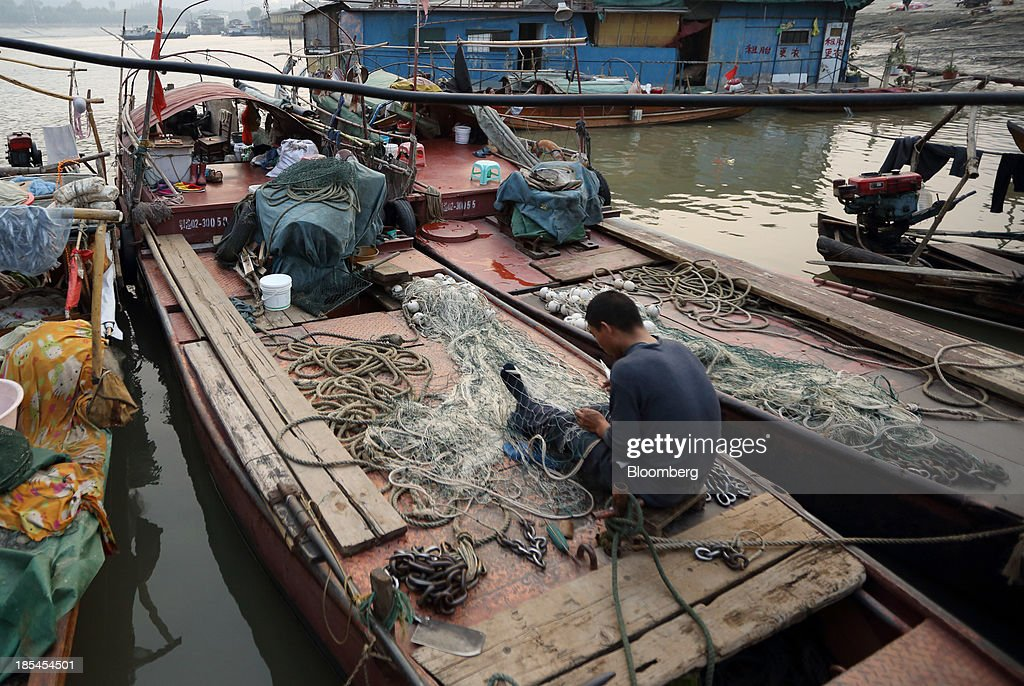 A fisherman takes care of his fishing net on a boat on the Chang Jiang river in Wuhan, China, on Sunday, Oct. 20, 2013. China's economic expansion accelerated to 7.8 percent in the third quarter from a year earlier, the statistics bureau said Oct. 18, reversing a slowdown that put the government at risk of missing its 7.5 percent growth target for 2013. Photographer: Tomohiro Ohsumi/Bloomberg via Getty Images