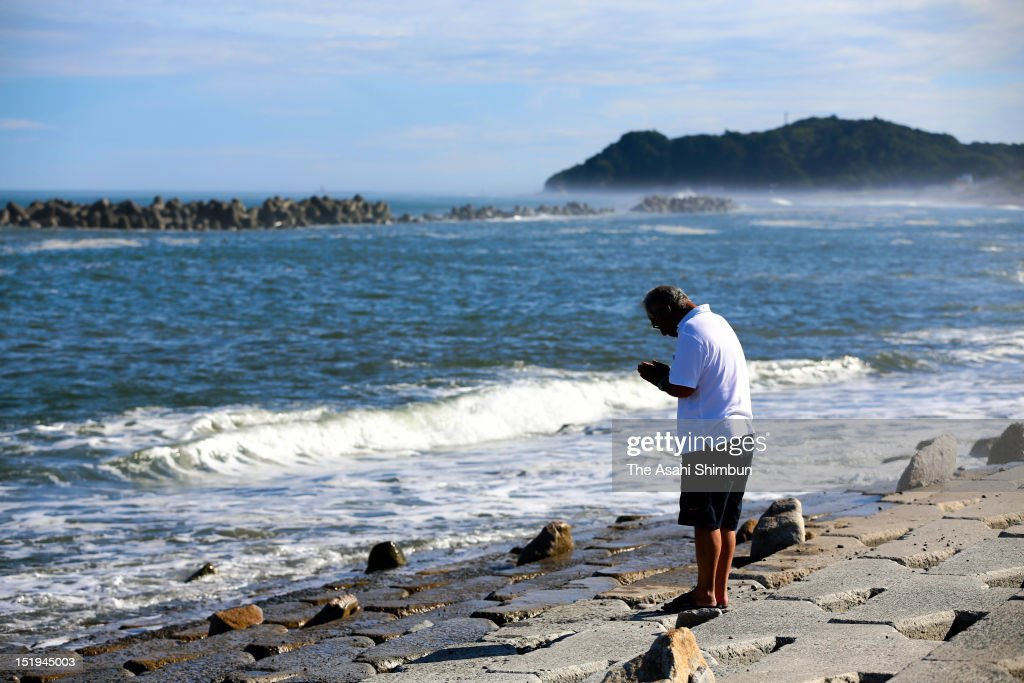 Fisherman Tatsuo Niizuma, 69, prays for his missing daughter Ikumi, on September 11, 2012 in Iwaki, Fukushima, Japan. Ikumi once evacuated to the hill with her family, was hit by the tsunami when she returned her home to take her dog. 18 months on, still 2,814 people are missing and 340,000 people are forced to live at temporary housing.