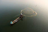 Fisherman throwing a net over the Taungthaman lake