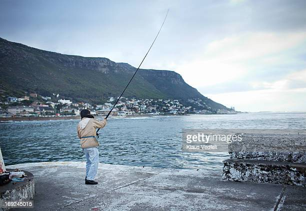 Fisherman throwing line out in the ocean