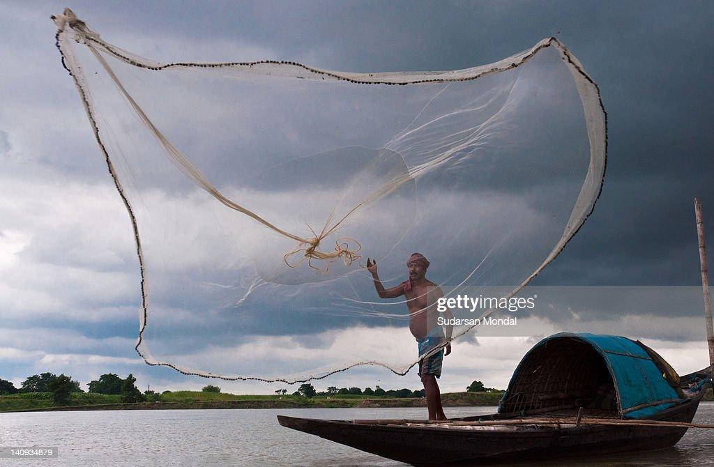 Fisherman throwing net for fishing : Stock Photo