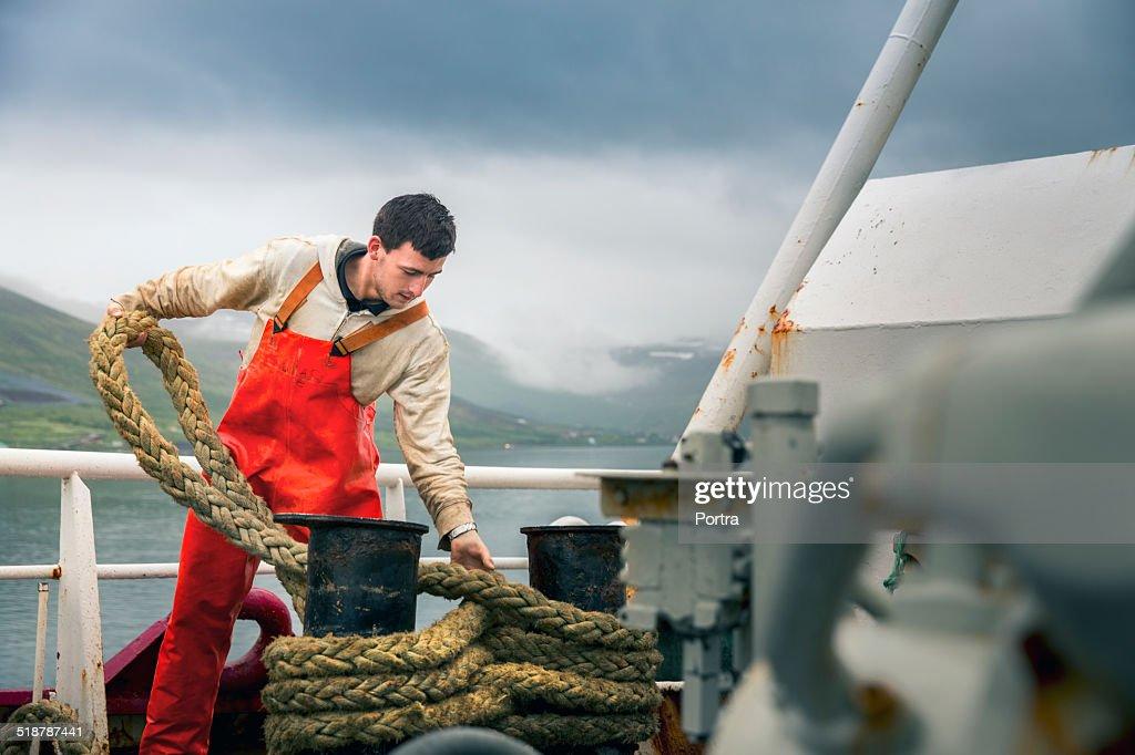 Fisherman tying rope on boat