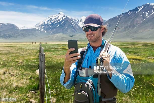 Fisherman Using His Phone In A Beautiful Mountain Meadow
