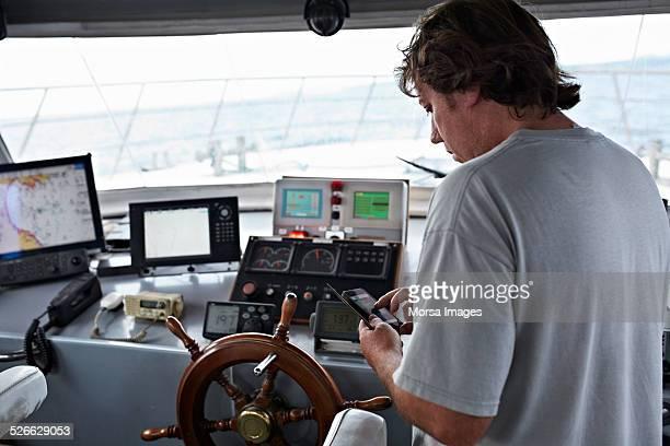 Fisherman using smart phone in boat