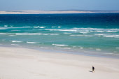 Fisherman walking on Almonta Beach. Australia.