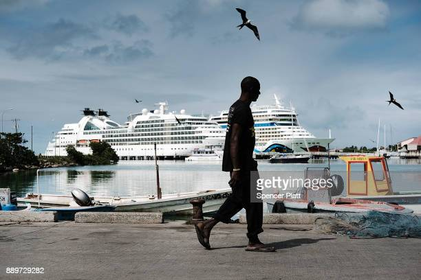 A fisherman walks by cruise ships as they sit in the harbor on December 10 2017 in St John's Antiqua While it's sister island Barbuda was nearly...