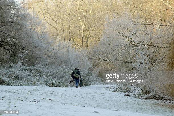 A fisherman walks through the frost near Wallingford Oxfordshire after one of the coldest nights of the autumn so far this year across England and...