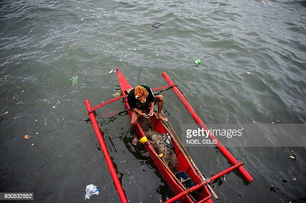TOPSHOT A fisherman wearing tiger headgear collects his catch from a net in Baseco Manila on December 26 2016 Typhoon NockTen which made landfall on...