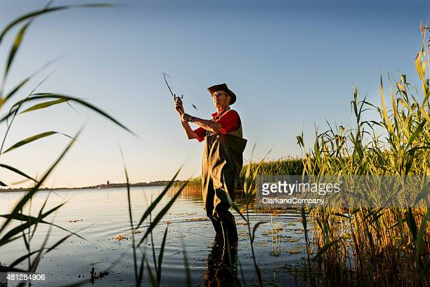 Fisherman Wearing Waders Casting His Line Out