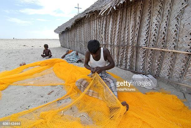 Fisherman weaving a fishing net