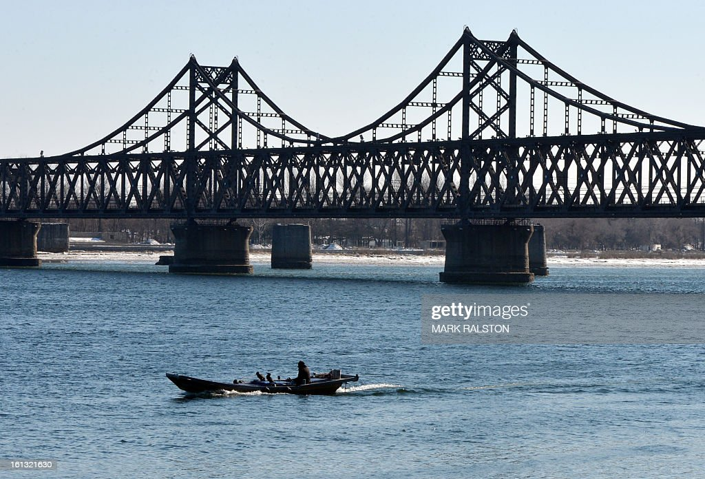 A fisherman who uses Cormorant birds to catch fish passes beneath the Sino-Korean Friendship bridge that links the North Korean town of Sinuiju with the Chinese town of Dandong on February 10, 2013. US Secretary of State John Kerry warned that North Korea's expected nuclear tests only increase the risk of conflict and would do nothing to help the country's stricken people. The country has vowed to carry out a third nuclear test soon, and concerns have been raised over the type of fissile material used in the device. AFP PHOTO/Mark RALSTON