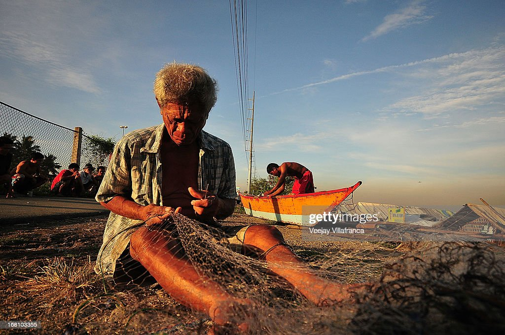 A fisherman who was a f ormer residents of Freedom Island prepares to head out into the bay on May 5, 2013 in Manila, Philippines. Around 13,000 hectares of the coastal area is to be recalimed and developed under the Public Private Partnership (PPP) of the Philippine government.