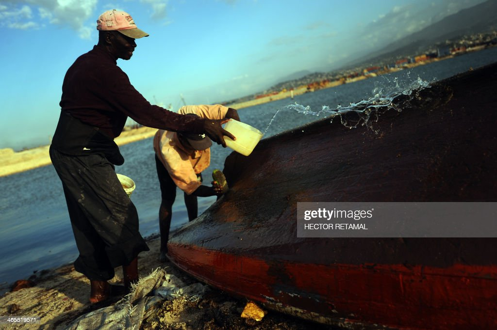 Fisherman Wilson (R), 25, cleans his small boat with his father (L) near of the Wharf Jeremie, in La Saline neighborhood, in Port au Prince, on January 27, 2013. AFP PHOTO/Hector RETAMAL