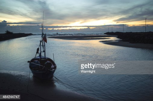 fisherman with a boat on the ocean shore at sunset : Stock Photo