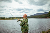 Fisherman with a fishing rod. Summer fishing on the lake.