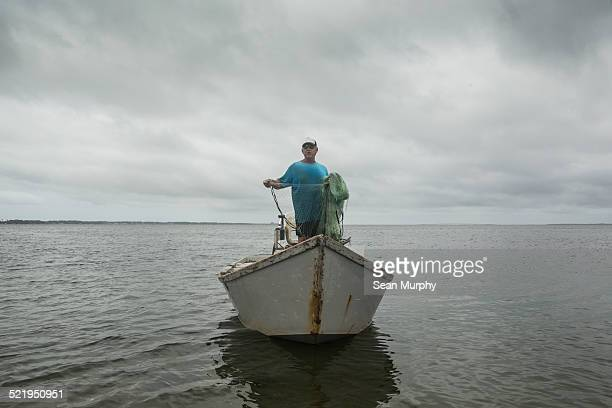 Fisherman with Cast Net on a Boat