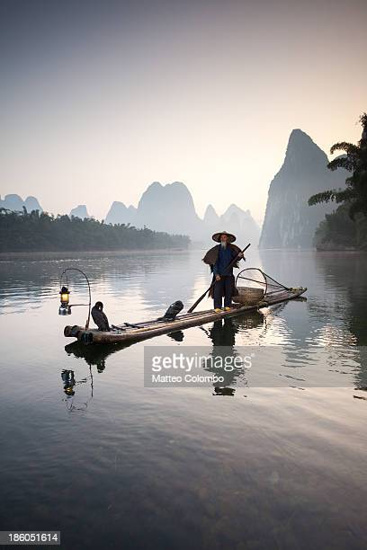 Fisherman with cormorants on river, Guilin, China