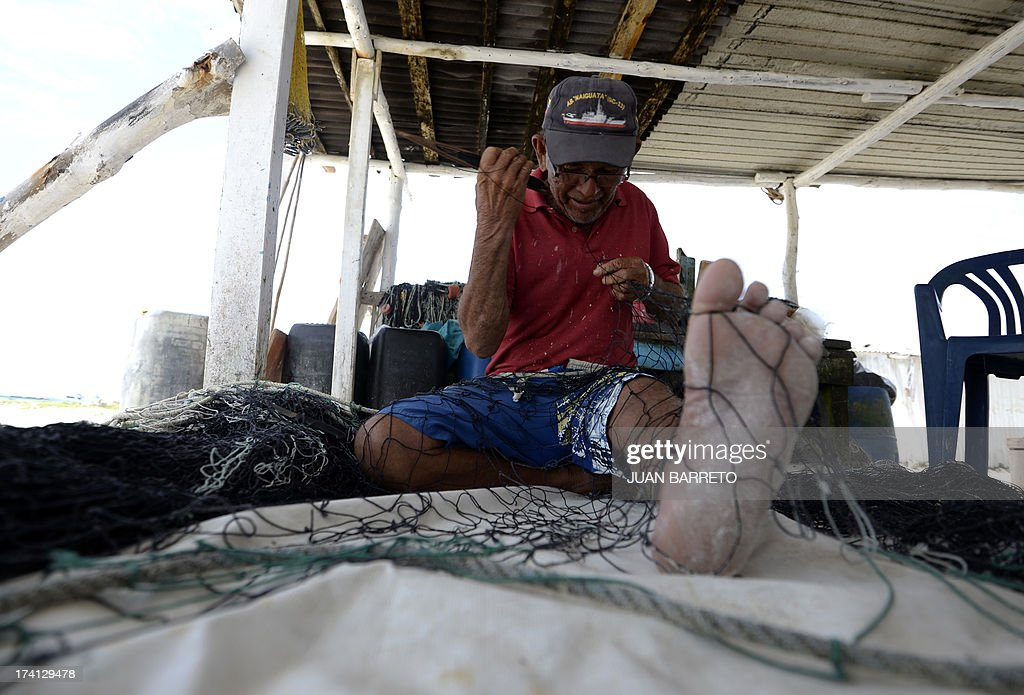 A fisherman works on a fishing net before going fishing in La Tortuga island, in the southern Caribbean Sea, during an inspection by the Venezuelan Tourism Minister on July 20, 2013. The government suspended by 30 days the tourist boats arriving to the island to complete a clean-up operation.