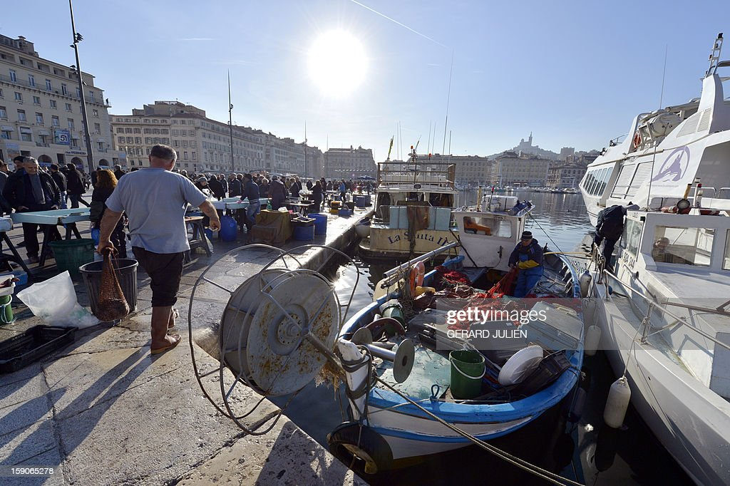 A fisherman works on his boat next to a fish market on January 7, 2013 in the Vieux Port of Marseille (Marseille's old harbor), southern France, before the launching on January 12, 2013 of 'Marseille-Provence European Capital of Culture' in 2013.