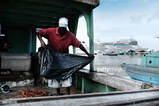 A fisherman works on his boat on December 10 2017 in St John's Antiqua While it's sister island Barbuda was nearly destroyed by Hurricane Irma...
