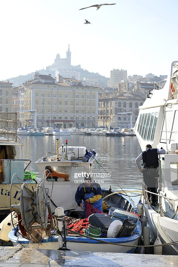 A fisherman works on his boat on January 7, 2013 in the Vieux Port of Marseille (Marseille's old harbor), southern France, before the launching on January 12, 2013 of 'Marseille-Provence European Capital of Culture' in 2013.