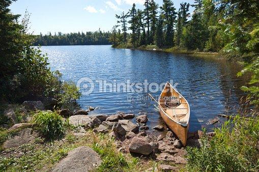 Fisherman's canoe on rocky shore in northern Minnesota lake : Stock Photo
