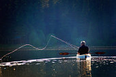 A fisherman casting on a lake from a kayak, backlit by the afternoon sun