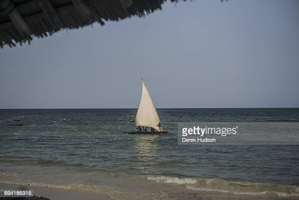 A fisherman's simple dugout boat with outriggers sails past a tourist resort bungalow nearby the beach at MsambweniThe small fishing town and...