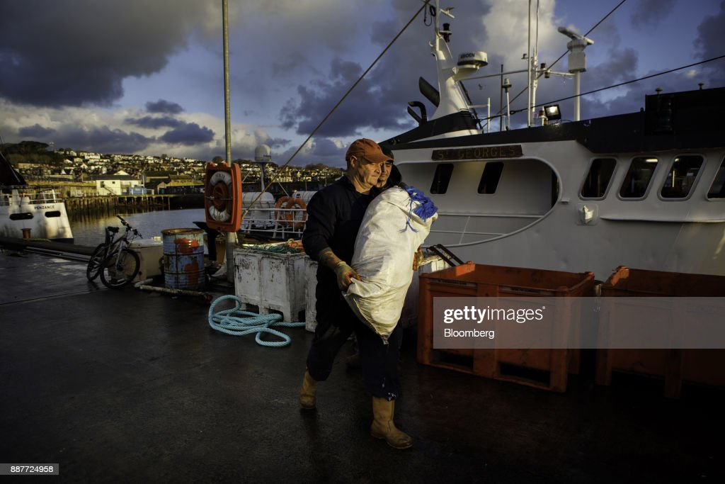 Fishermen and dock workers load nets onto the St. Georges fishing trawler at sunrise in Newlyn harbor in Newlyn, U.K., on Tuesday, Nov. 28, 2017. Prime Minister Theresa May will pull Britain out of the 1964 London convention that allows European fishing vessels to access waters as close as six to twelve nautical miles from the U.K. coastline. Photographer: Annie Sakkab/Bloomberg via Getty Images