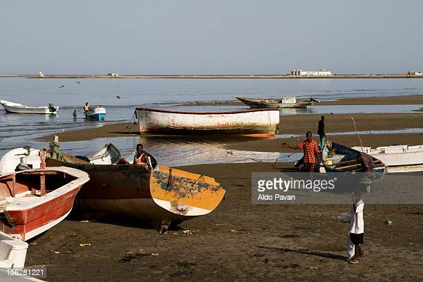 Fishermen and their boats at the low tide