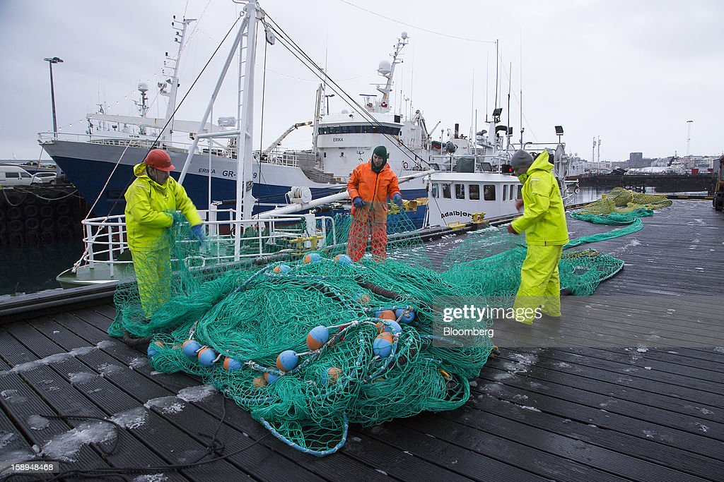 Fishermen arrange their nets beside fishing boats on the harborside in Reykjavik, Iceland, on Wednesday, Jan. 2, 2013. Creditors of Iceland's three biggest failed banks are fighting for a waiver to krona controls imposed in 2008 amid risks pay-outs will be delayed beyond 2015. Photographer: Arnaldur Halldorsson/Bloomberg via Getty Images